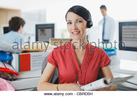 Businesswoman working at desk in headset - Stock Photo