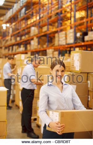 Workers packing boxes in warehouse - Stock Photo
