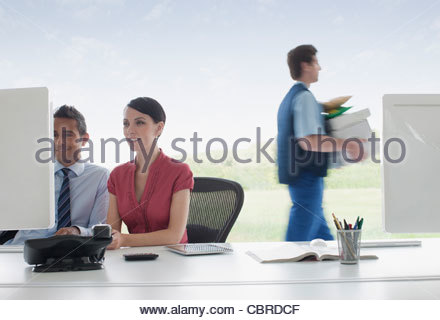 Deliveryman walking past business people working in office - Stock Photo