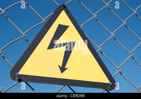 electrical hazard sign placed on a metal fence - Stock Photo