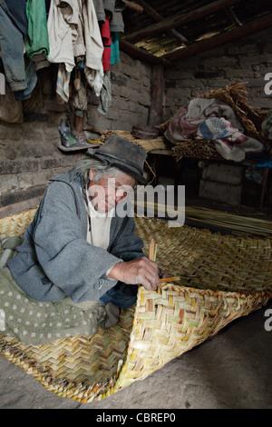 Man weaving a traditional straw carpet in a village near Otavalo, Ecuador. - Stock Photo