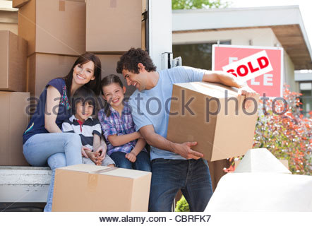 Family unloading boxes from moving van - Stock Photo