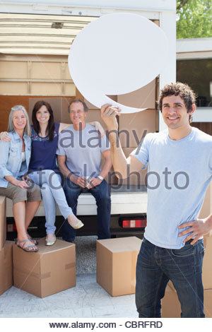 Friends unloading moving van, one man holding comment bubble - Stock Photo