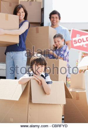 Boy playing in box near moving van - Stock Photo