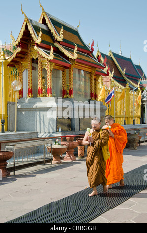 Two Buddhist monks with eyes closed & hands cupped in prayer walk around stupa at a Buddhist temple in Lamphun Thailand - Stock Photo