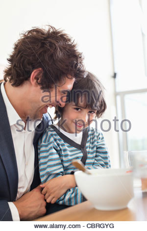 Father and son eating breakfast together - Stock Photo