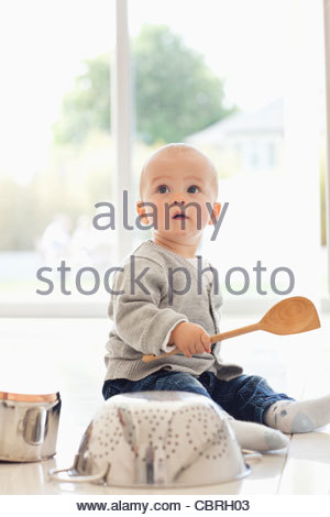 Baby banging on pots and pans - Stock Photo