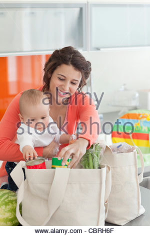 Woman holding baby and unloading groceries from reusable bag - Stock Photo