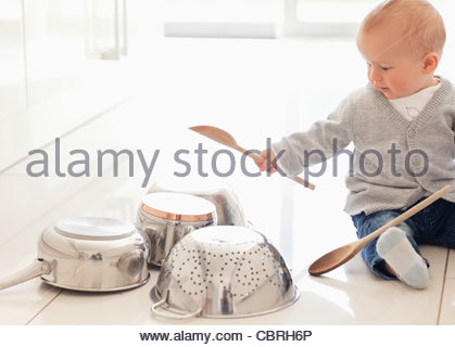 Baby banging on pots with wooden spoon - Stock Photo