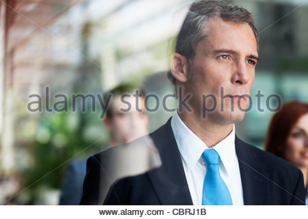 Serious businessman looking out window - Stock Photo