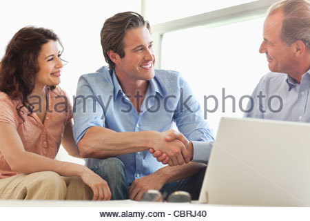 Couple shaking hands with financial advisor - Stock Photo