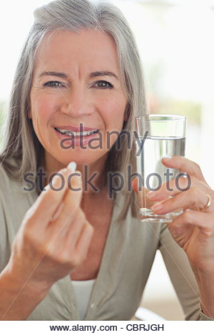 Woman holding glass of water and taking pill - Stock Photo