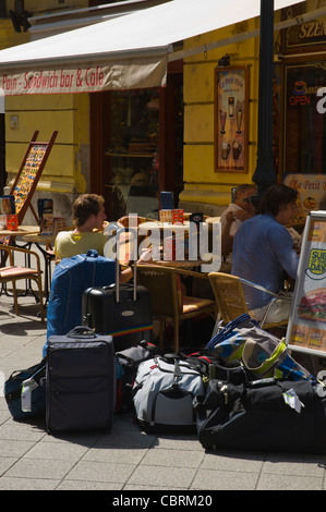 Tourists with suitcases on cafe terrace along Vaci utca street central Budapest Hungary Europe - Stock Photo