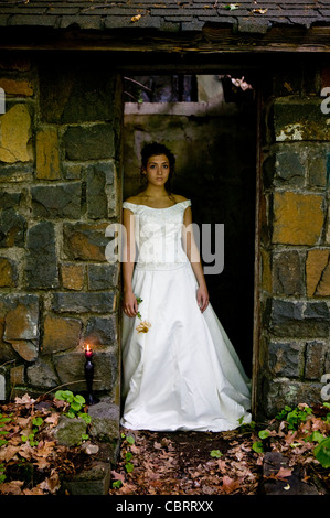 Bride in doorway of stone cottage. - Stock Photo