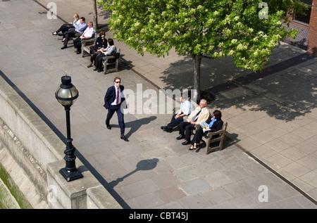 Lunchtime break for office workers on the Thames waterfront walkway below Millenium Bridge, Blackfriars, London, - Stock Photo