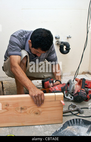 Hispanic man from Mexico working his own construction business in the USA replaces support beam in upstairs bathroom - Stock Photo