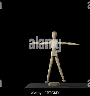 studio photography of a wooden artist doll standing on a desktop in black back, with copyspace - Stock Photo