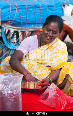 Indian woman sitting on an indian street sieving red coloured powder to remove bits . Puttaparthi, Andhra Pradesh, - Stock Photo
