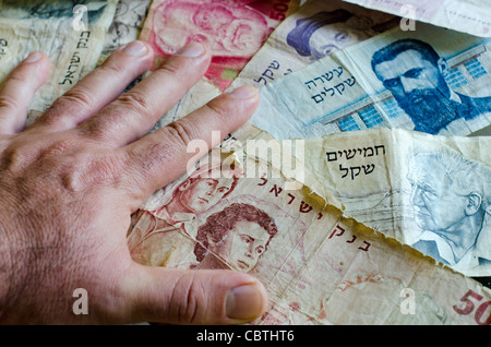 Man hand counting old Israeli money currency. - Stock Photo