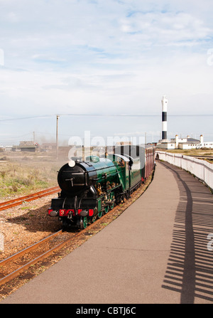 Romney, Hythe and Dymchurch Railway train with the lighthouse in the background, Dungeness, Kent, UK - Stock Photo