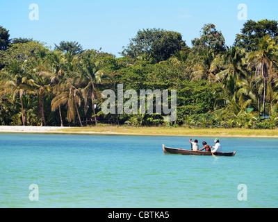 Dugout canoe with amerindian people near a beach in Bocas del Toro, caribbean sea, Panama - Stock Photo