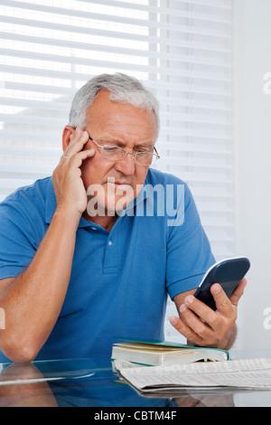 Serious senior man looking at calculator - Stock Photo