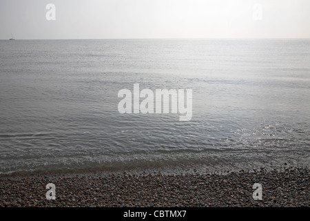 Grey calm water of the North Sea with gentle waves on a still day, from Shingle Street, Suffolk, England - Stock Photo