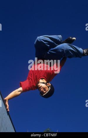 Teenage boy inline skating on the vert ramp. - Stock Photo