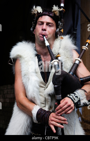 Man dressed in animal furs, playing the bagpipes in High Street, Edinburgh, at the fringe Festival. Scotland, UK, - Stock Photo