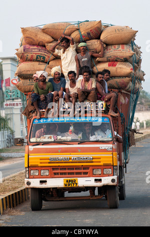 Overloaded Indian lorry carrying sacks of rice and farm workers . Andhra Pradesh, India - Stock Photo