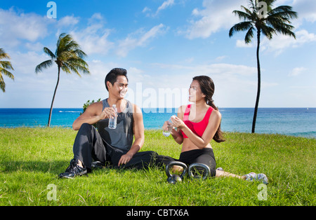 Couple drinking water after exercise at waterfront - Stock Photo