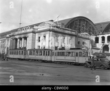 trolley cars parked in front of stone building - Stock Photo