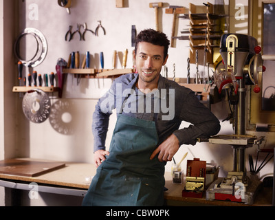 Portrait of adult italian man at work as craftsman in shop with tools in background - Stock Photo
