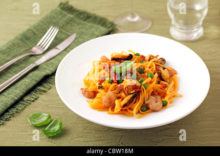 Orange spaghetti with mussels and prawns. Recipe available. - Stock Photo