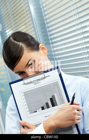 Image of sad businesswoman with document thinking of something in office - Stock Photo
