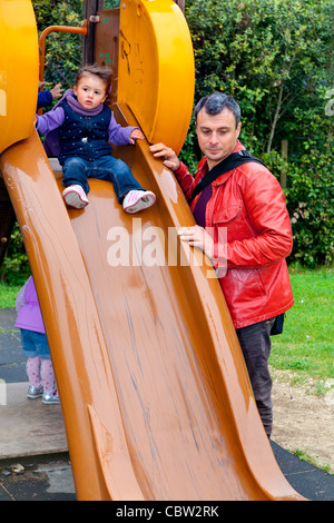 Father and daughter on a playground slide - Stock Photo