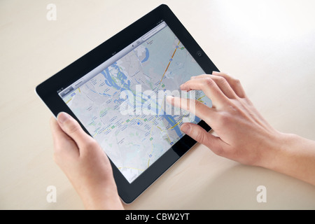 Woman hands holding and touching on Apple iPad2 with Google Maps application on a screen. - Stock Photo
