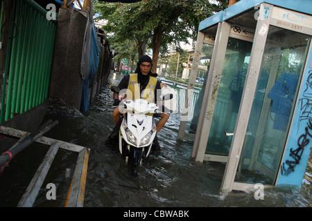 Motorcycle driving on flood street in Bangkok - Stock Photo