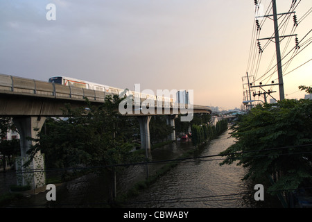BTS Sky train over floodwaters on street in Bangkok - Stock Photo