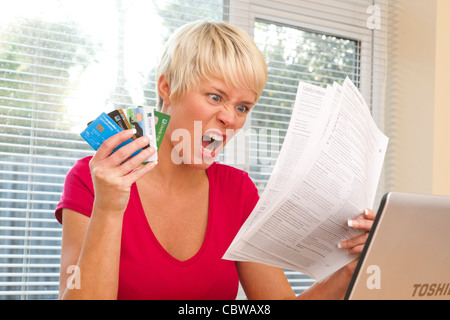 woman shocked at credit card statements - Stock Photo