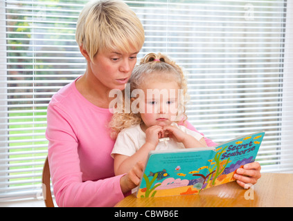 mother teaching young daughter to read from a book - Stock Photo