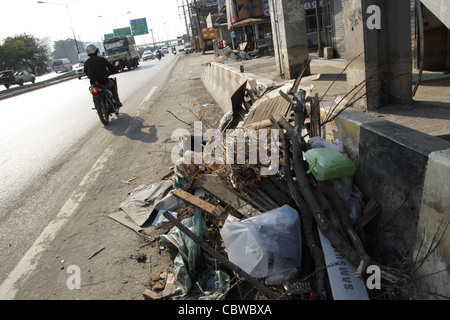 Garbages on main street after floodwater reduced - Stock Photo