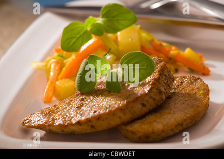 fried lamb steak with vegetables on white plate - Stock Photo