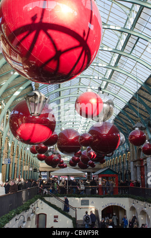 Christmas decoration red balls hanging from roof inside Covent Garden market. London Uk - Stock Photo
