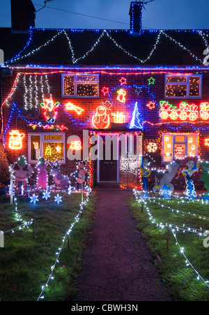 Exterior Of A House Lit Up With Christmas Lights At Dusk Home Property Illuminated Xmas Decorations At Night - Stock Photo