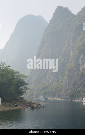 Cruise ship and sightseeing rafts on the hazy Li River in China among the tall karst peaks of Guangxi - Stock Photo