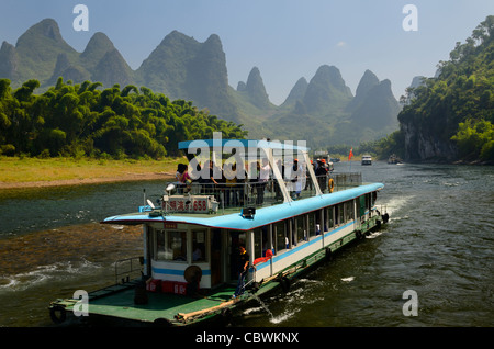 Tour boat cruise down the Li river with bamboo forest and hazy karst peaks Peoples Republic of China - Stock Photo