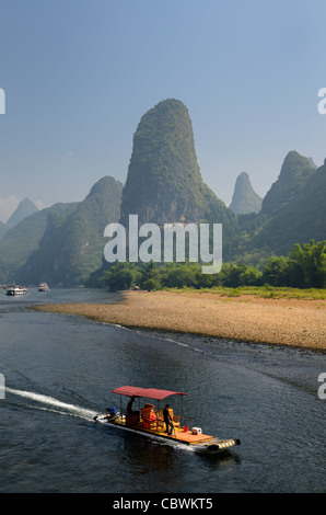 Tour boat raft traveling down the Li river Guangxi China with tall karst mountain cones - Stock Photo