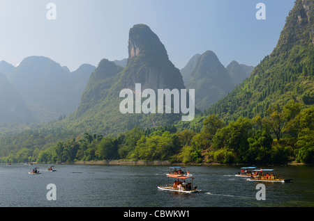 Tour boat rafts on the Li river Guangxi with pointy karst mountain peaks in the haze Peoples Republic of China - Stock Photo