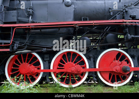 Red wheels of old locomotive, trains powered by steam - Stock Photo